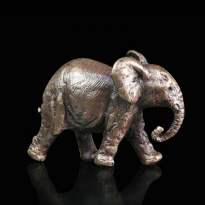 minature bronze elephant walking along