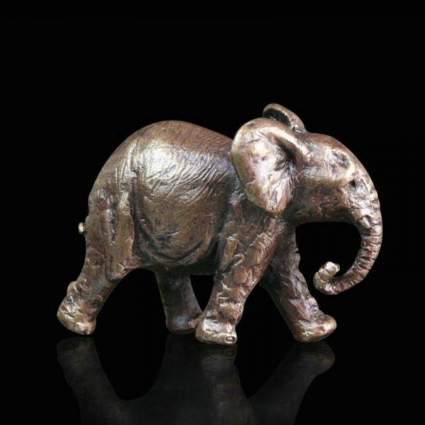 minature bronze elephant walking along
