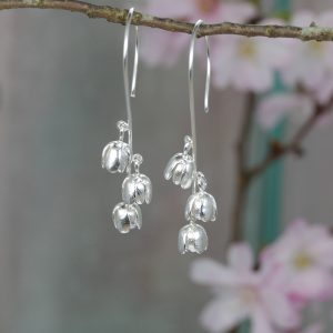 three tiny silver bluebell flower earrings on long hook wires